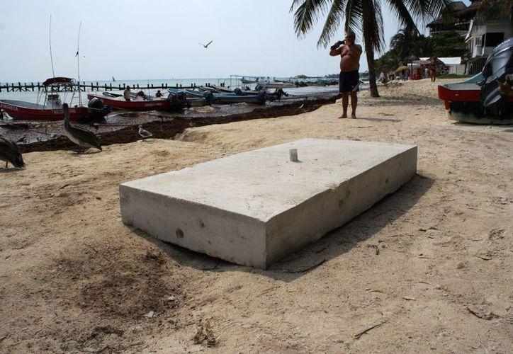 Algunos durmientes que servirán para frenar en sargazo dentro del mar, descansan sobre la arena. (Octavio Martínez/SIPSE)