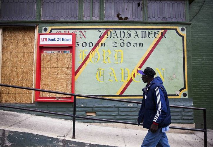 Las tensiones en Baltimore y en Ferguson, Missouri, entre otros lugares, fuerzan a los candidatos a indagar en las relaciones complejas entre las comunidades pobres y la policía. Foto de un hombre que camina frente a la Taverna Oxford, dañada por los disturbios en Baltimore. (AP Foto/David Goldman, File)