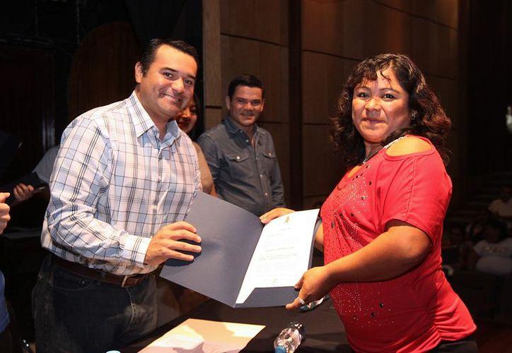 La subcomisaria de Noc Ac, María Maribel Huchim Ramos, recibe su constancia de manos del Alcalde Renán Barrera. (Cortesía)