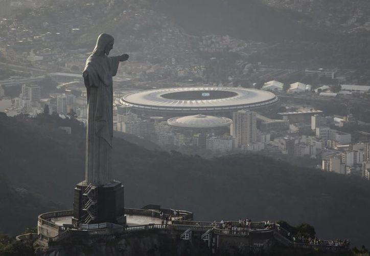 Esta imagen del 13 de mayo de 2014 muestra una vista aérea del estadio Maracaná detrás de la estatua del Cristo Redentor a través de la ventana de un avión en Río de Janeiro, Brasil (Felipe Dana/AP)