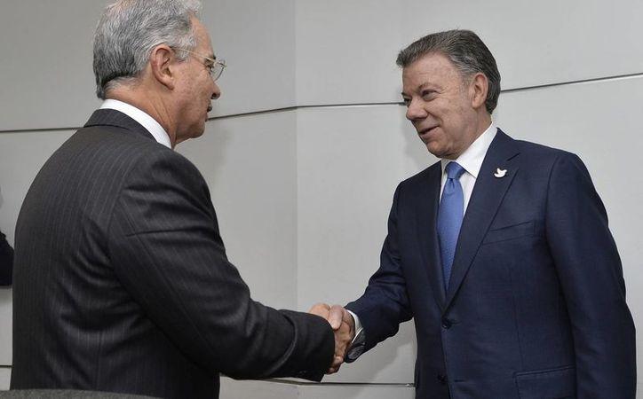 El de este miércoles es el primer encuentro que sostienen en cinco años Álvaro Uribe y Juan Manuel Santos, quienes rivalizaron por sus posturas respecto a las FARC. (EFE)