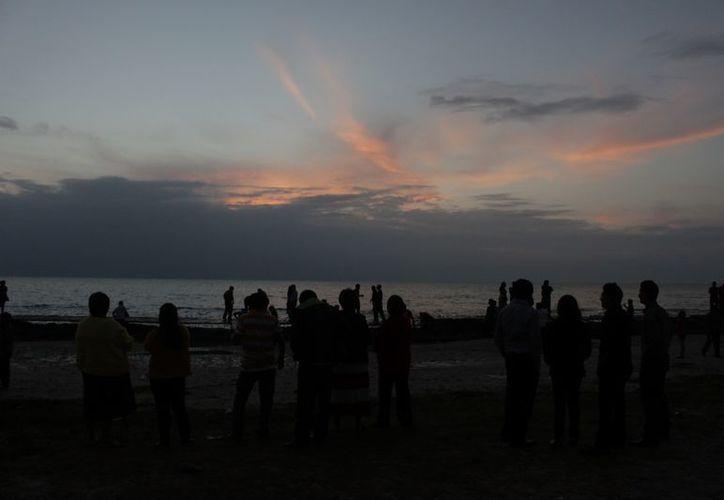 Pese a inesperado aguacero, quienes se quedaron en el bulevar Bahía para ver el amanecer tuvieron justo premio a su espera. (Francisco Sansores/SIPSE)