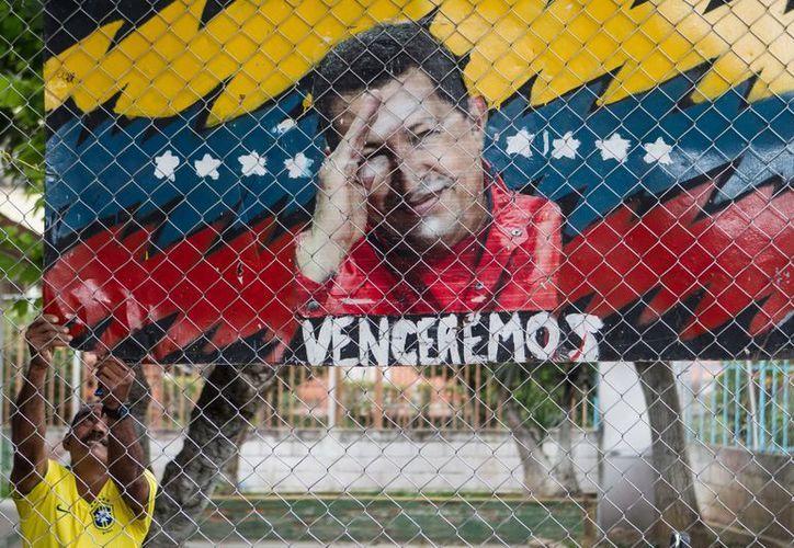 Un hombre cuelga un cartel alegórico al presidente de Venezuela, Hugo Chávez. (EFE)