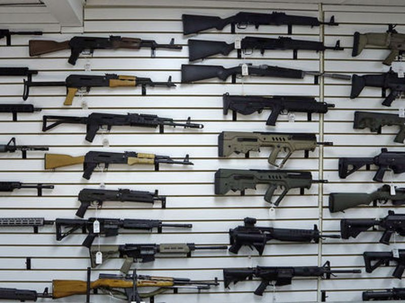 this file photo shows dozens of semi-automatic rifles on a wall in a gun shop in Lynnwood, Wash.
