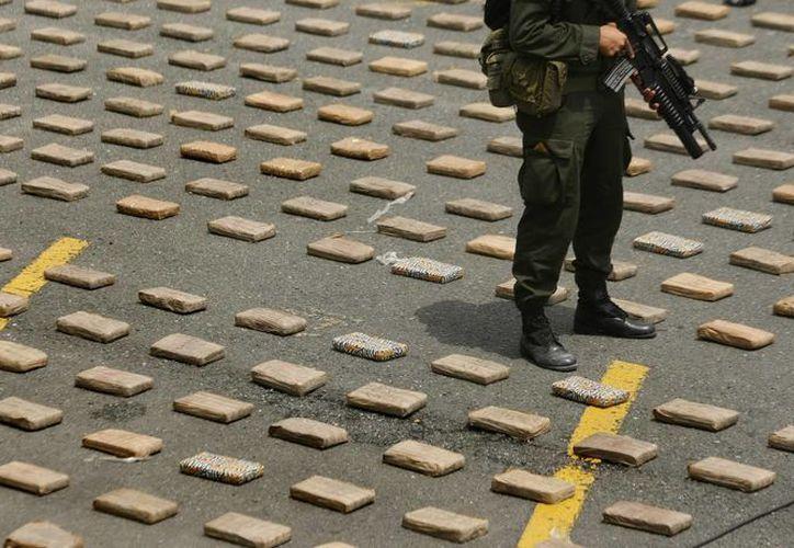 Un miembro de la policía custodia paquetes con droga incautada por las autoridades colombianas. (Archivo/EFE)