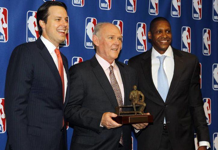 George Karl (c) recibe la distinción en compañía del presidente de los Nuggets, Josh Kroenke (i) y el manager general Masai Ujiri. (Agencias)