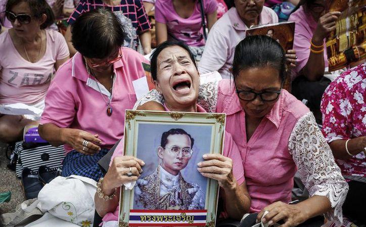 Una mujer tailandesa llora abrazada a un retrato del rey Bhumibol Adulyadej frente al hospital Siriraj en Bangkok, Tailandia, en donde murió el monarca. (EFE)
