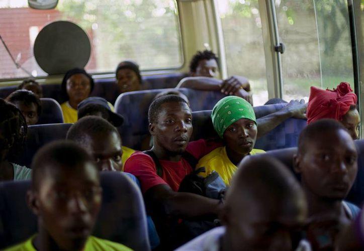 La foto de archivo del 24 de noviembre de 2013 muestra a haitianos que viajan a su país tras haber sido deportados de República Dominicana.  (Agencias)