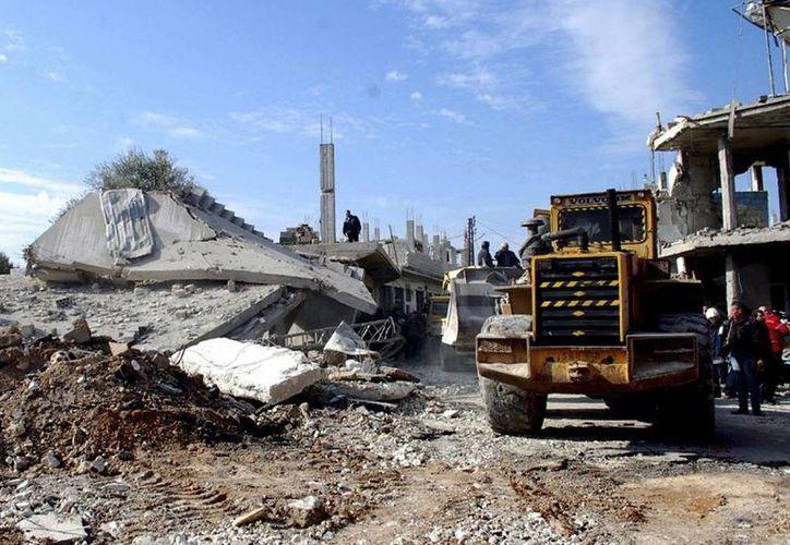 Al menos 8 rebeldes muertos por la explosión de un coche bomba en el norte de Siria. Foto de la agencia de noticias siria que muestra una excavadora retirando escombros de varias viviendas que resultaron destruidas tras la explosión de un coche bomba en la localidad de Al Kafat, en la provincia de Hama, el pasado 9 de enero. (Archivo/Efe)
