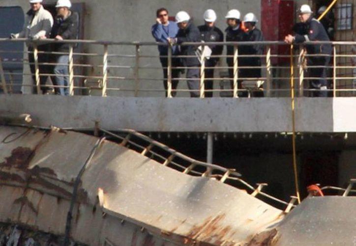 El comandante Francesco Schettino (sin casco), capitán y principal imputado del naufragio del crucero Costa Concordia, en el que murieron 32 personas, sube a bordo de la embarcación que yace frente a la isla italiana del Giglio. (EFE)