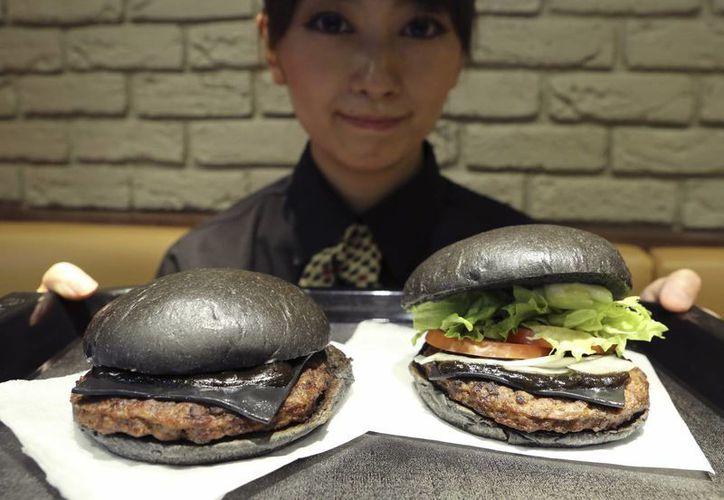 Una empleada de Burger King muestra la hamburguesa Kuro Diamante (der) y la hamburguesa Kuro Perla. (Agencias)