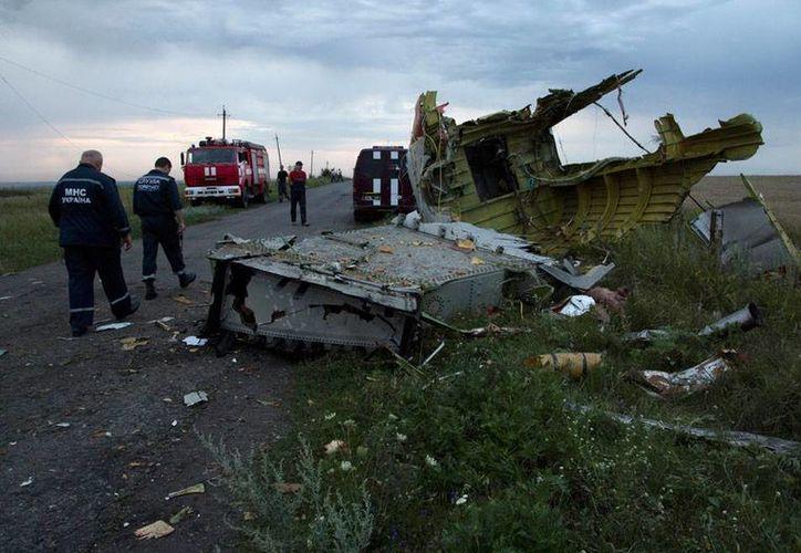 Bomberos inspeccionan el sitio donde cayó el avión de Malaysia Airlines, que transportaba 295 personas y fue derribado este miércoles en Ucrania. (Foto: AP)