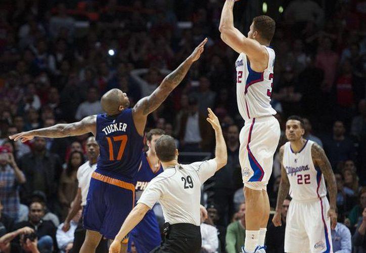Blake Griffin encesta a pesar de la marcación de P. J. Tucker en partido entre Clippers y Suns en la NBA. (Foto: AP)