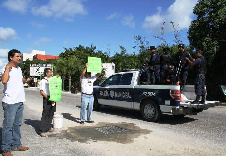 Un grupo de ciudadanos reparó una coladera abierta en el Arco Vial de Playa del Carmen, a modo de protesta. (Octavio Martínez/SIPSE)