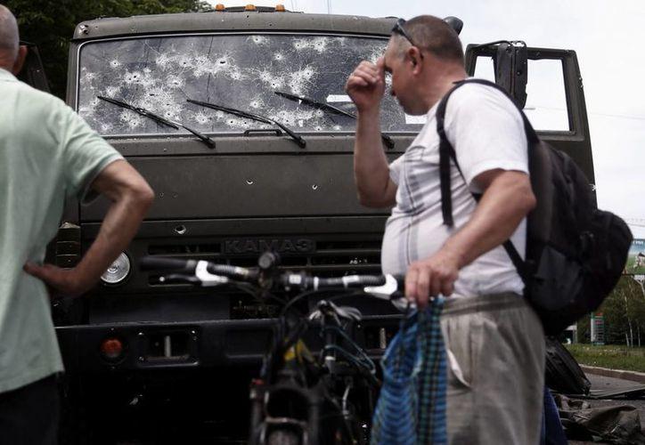 Un hombre reacciona al ver los agujeros de bala en un camión, en las inmediaciones del aeropuerto de la región rebelde de Donetsk, Ucrania. (EFE)