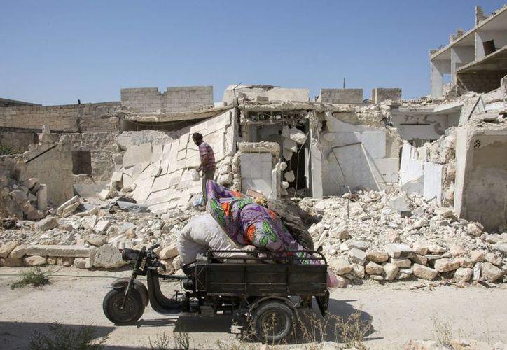 Un hombre pasa con sus escasas pertenencias por delante de unos edificios destruidos en Alepo. (Archivo/EFE)