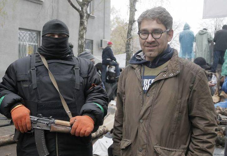 En imagen tomada el 13 de abril de 2014 el periodista Simon Ostrovsky (der) posa junto a un hombre armado simpatizante de Rusia. (Agencias)