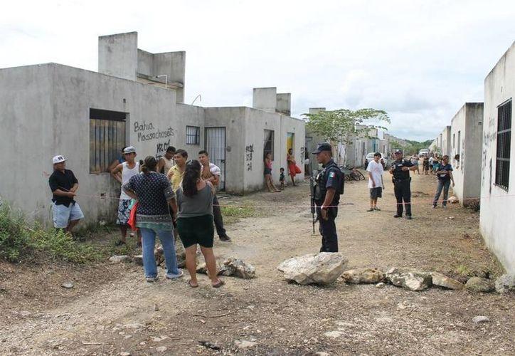 Elementos de la Policía Municipal impidieron que una familia sea instalada a la fuerza en una de las casas abandonadas del fraccionamiento In House.  (Adrián Barreto/SIPSE)