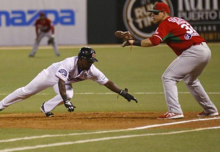 Elián Herrera (i), de los Gigantes del Cibao de Rep. Dominicana, al regresar a primera base, custodiada por Joey Meneses (d) de Tomateros de Culiacán de México, durante el partido de la Serie del Caribe. (EFE)