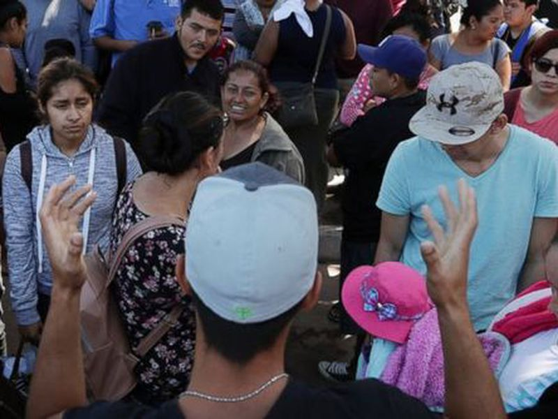 In this June 13, 2018 photo, an organizer, foreground, speaks to families as they wait to request political asylum in the United States, across the border in Tijuana, Mexico.  (AP)