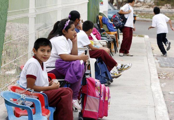 En primaria, a pesar de los avances tecnológicos, padres de familia tienen que montar guardia ante las escuelas para conseguir un lugar para sus hijos. (Juan Albornoz/SIPSE)