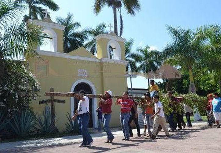 Los participantes cargaron el árbol desde el santuario de la cruz parlante hasta la puerta de la iglesia del parque central. (Redacción/SIPSE)