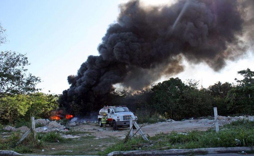 Dos elementos del departamento de Bomberos sofocaban las llamas que alcanzaron 10 metros de altura. (Redacción/SIPSE)