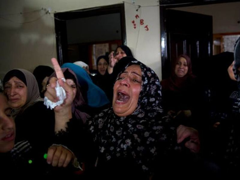 Relatives of 15-year-old Othman Hilles, mourn during his funeral in the family home in Gaza City.