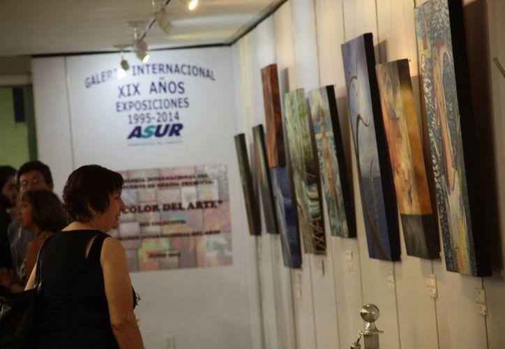 Una mujer observa la exposición del colectivo Corredor Internacional del Arte en el Aeropuerto Internacional de Mérida, inaugurado el miércoles 17 de junio de 2015. (Milenio Novedades)