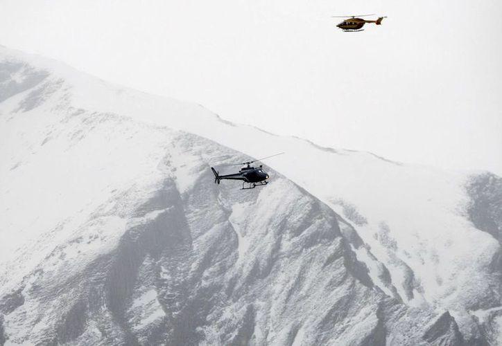 Helicópteros de rescate sobrevuelan la ladera de la montaña cerca de Seyne-les-Alpes, lugar donde se estrelló un avión pasajeros de Germanwings. (Agencias)