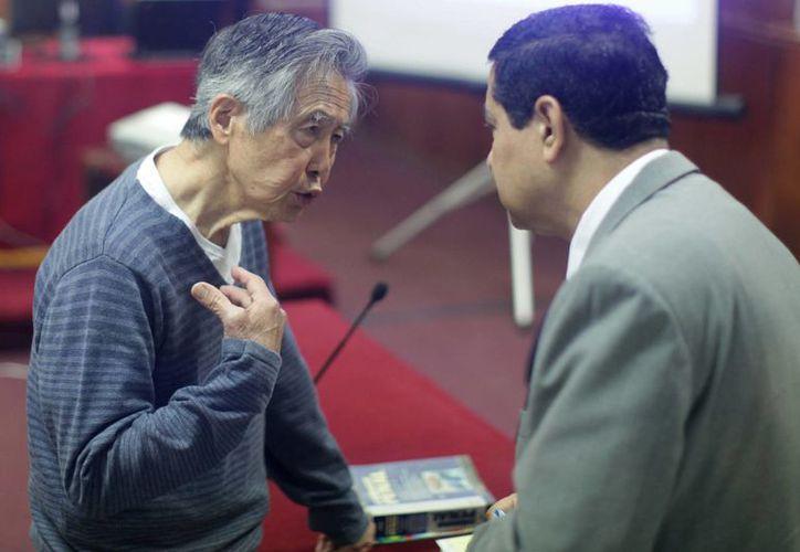 Fujimori (i) conversa con su abogado William Castillo en el juicio que se le sigue por su presunta participación en la compra de la línea editorial de diarios sensacionalistas durante su gobierno. /Archivo/EFE)