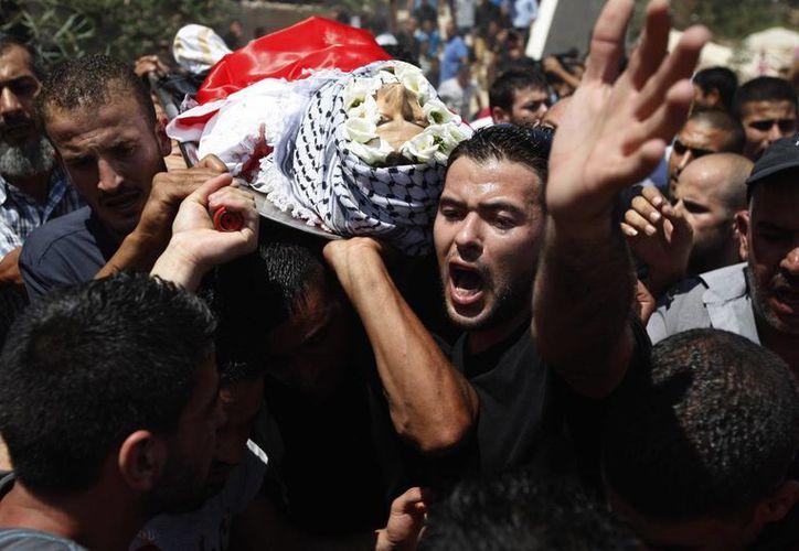 Palestinos cargan el cadáver de uno de sus compatriotas -muerto por militares israelíes- durante su funeral.  (Agencias)
