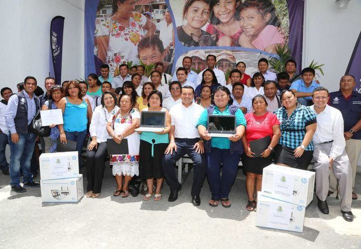 El alcalde de Mérida, Renán Barrera Concha, posa con los comisarios que recibieron equipo de cómputo. (SIPSE)