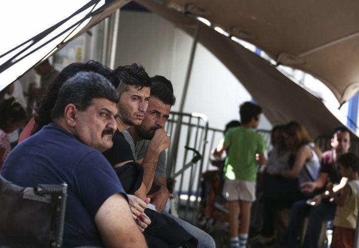 Refugiados esperan su turno para que un comité les de una audiencia de asilo en el servicio de Asilo de Grecia. (AP/Yorgos Karahalis)