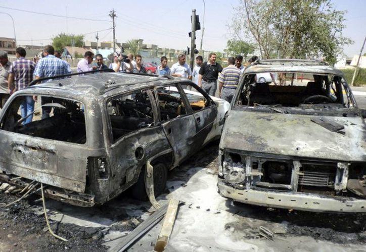Un grupo de civiles observa el lugar donde detonó un coche bomba. (EFE/Archivo)