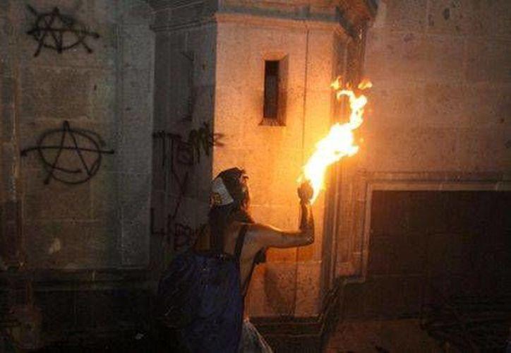 Uno de los manifestantes intentó prender fuego a la puerta del Palacio Nacional (Foto: Omar Franco/MILENIO)