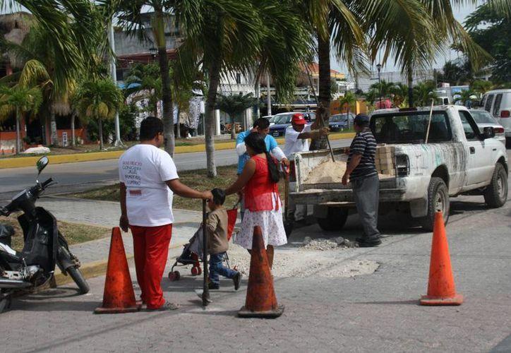 Los baches se rellenan con gravilla, y estos trabajos no mejoran la imagen de la avenida, mencionan comerciantes.  (Sara Cauich/SIPSE)