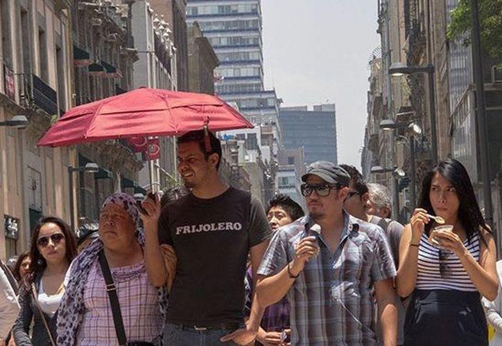 La gente se protege del intenso calor en la Ciudad de México. (Foto: Megalopolis)