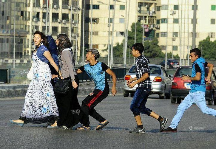 Tres jóvenes acosan a unas mujeres al cruzar una calle en El Cairo, Egipto, el 20 de agosto de 2012. (Foto de archivo: AP/Ahmed Abd El Latif, El Shorouk Newspaper)