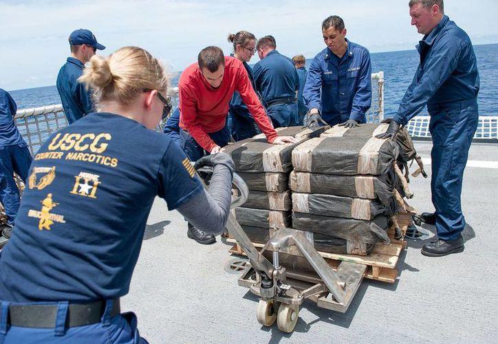 En imagen del 19 de julio de 2015, la tripulación de la embarcación Stratton de la Guardia Costera asegura paquetes de cocaína incautados de un semisumergible capturado en aguas internacionales frente a la región de Centroamérica. (Vía AP Foto/Contramaestre de 2da clase LaNola Stone/Guardia Costera de EU)