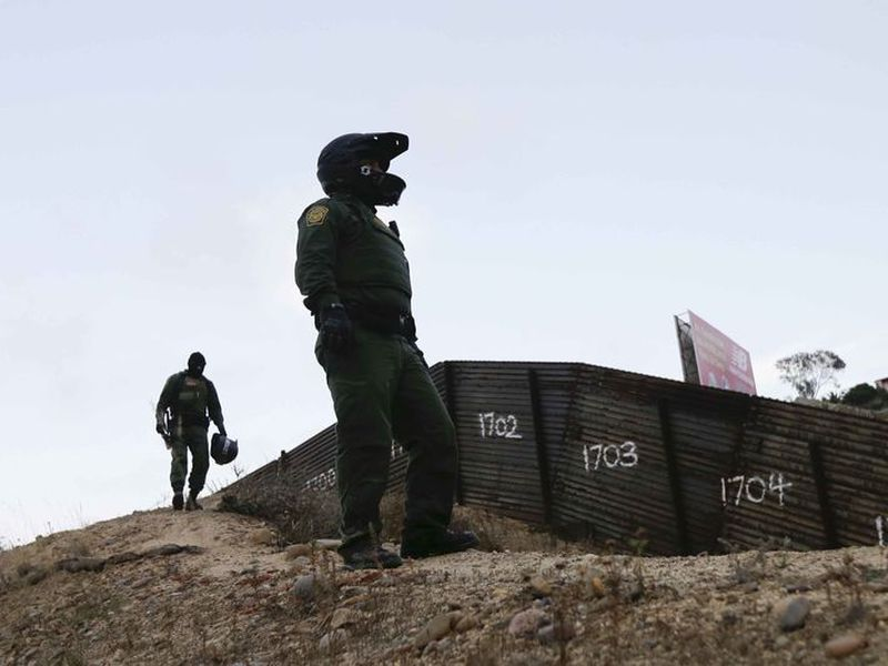 Border Patrol agents stands near a border structure in San Diego.