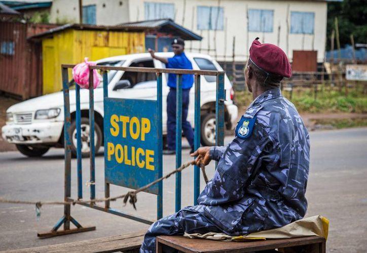 La policía custodia un control de carretera ante las ordenes del gobierno de Sierra Leona de hacer cumplir bloqueo de tres días para tratar de evitar que el ébola se siga propagando. (Agencias)