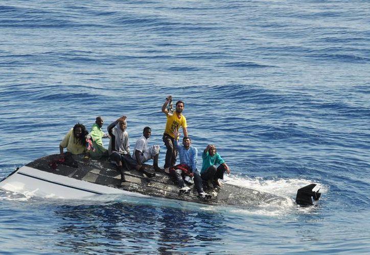 Esta foto del 6 de febrero de 2014 distribuida por la Guardia Costera de EU muestra a migrantes haitianos, indios y bahameños sobre un bote dado vuelta frente a la costa de Port Ste. Lucie, Florida.  (Agencias)