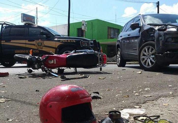 El motociclista se llevó la peor parte, ya que con todo y casco estrelló la cabeza contra una parte de la camioneta y luego cayó inconsciente al pavimento. (SIPSE)