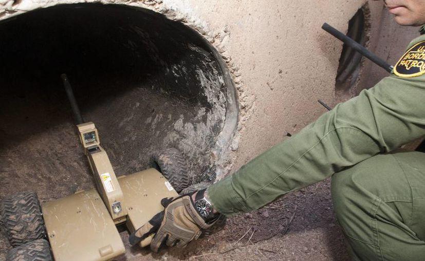 Un agente de la Patrulla Fronteriza de Tucson, Arizona, envía a un narcotúnel uno de los tres robots para rastrear su longitud en la frontera con México. (EFE)