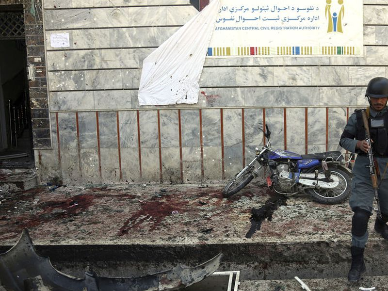 An Afghan police walks outside a voter registration center which was attacked by a suicide bomber in Kabul, Afghanistan.