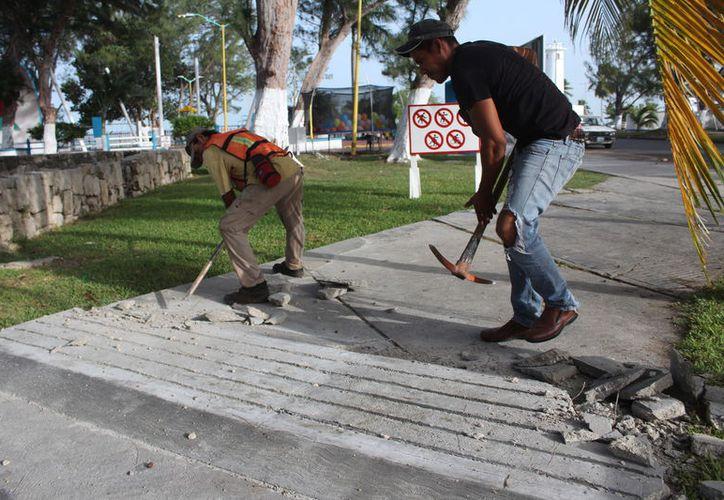 Trabajadores del Ayuntamiento de Othón P. Blanco retiraron ayer los topes que fueron colocados en una banqueta del Bulevar Bahía, de Chetumal. (Joel Zamora/SIPSE)