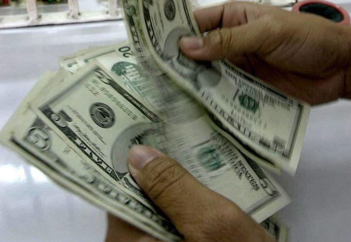 A la compra, la divisa norteamericana se situó en 14.43 pesos. (Foto de archivo)