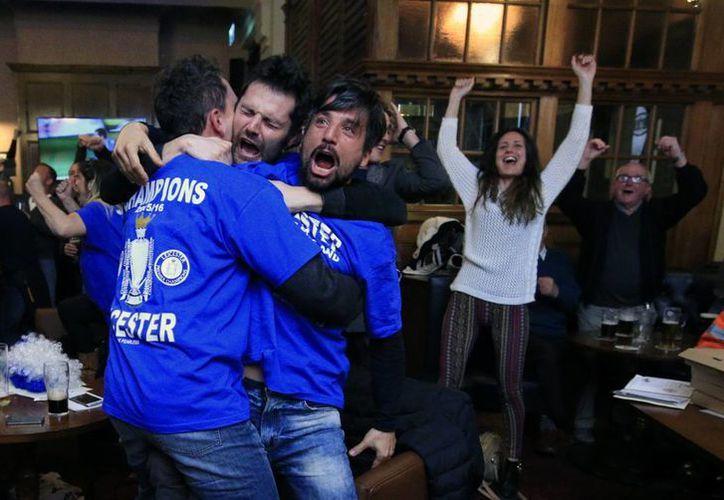 Fans del Leicester celebran el gol de Eden Hazard, del Chelsea, que empató 2-2 con Tottenham, resultado que dio el titulo de la Liga Premier este lunes al Leicester, que el domingo empató en casa del Manchester United. (Fotos: AP)