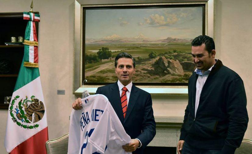 El beisbolista mexicano Adrián González, de Dodgers, quien podría ganar el premio Roberto Clemente, aparece en esta foto con el presidente Enrique Peña Nieto. (Notimex)